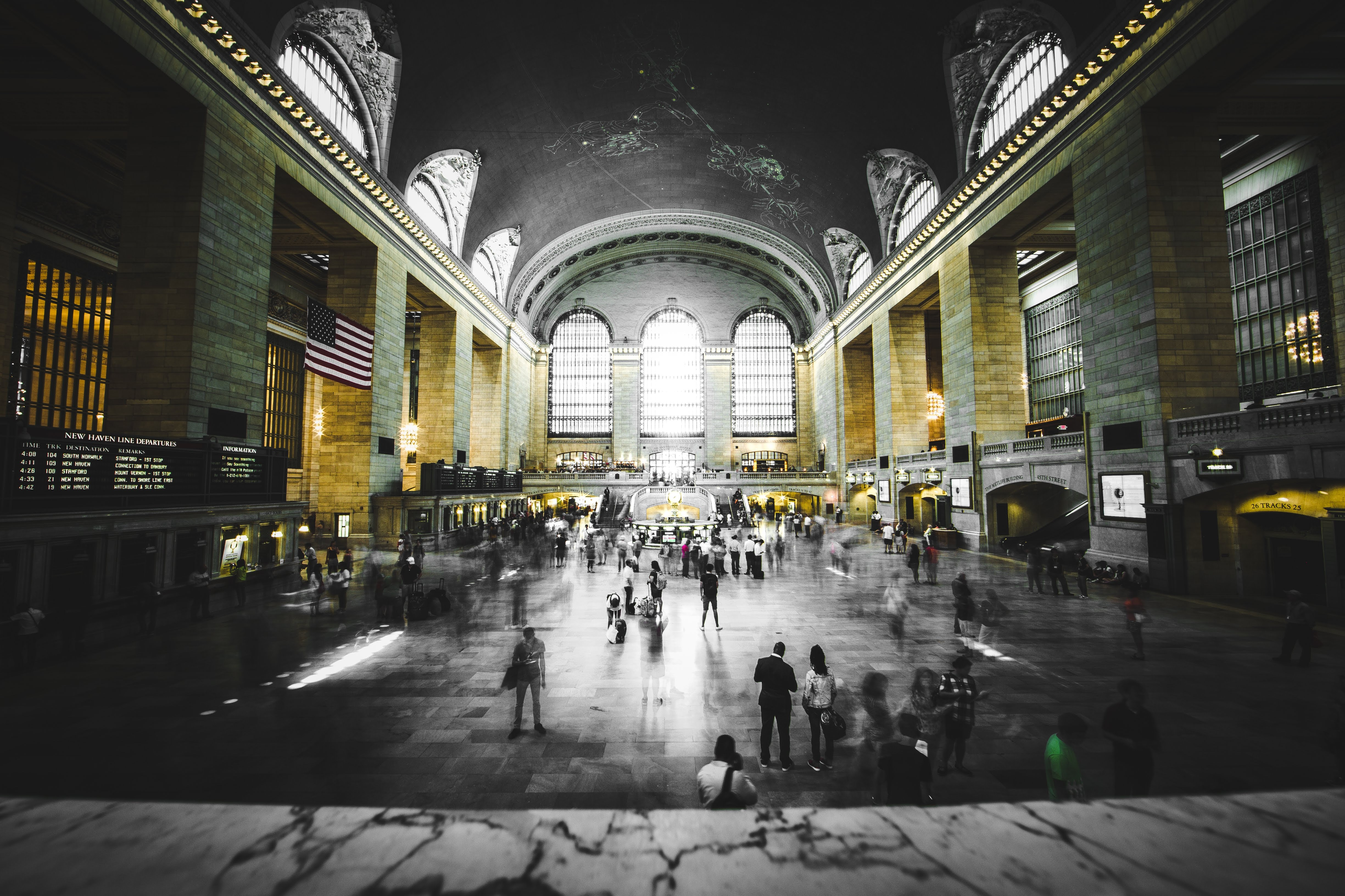 selective color photograph of people walking between structure columns