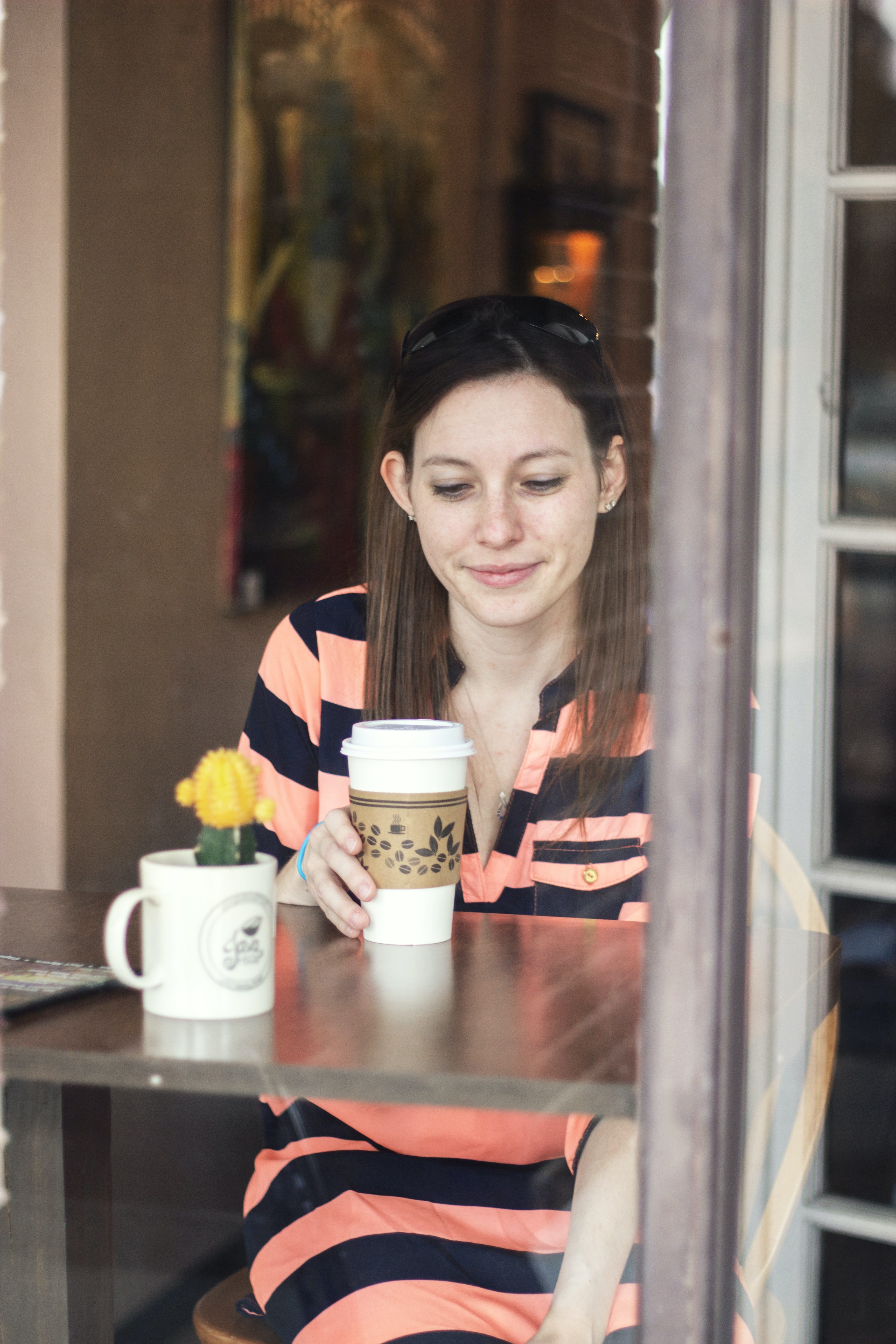 woman sitting down at table looking at cup in hand