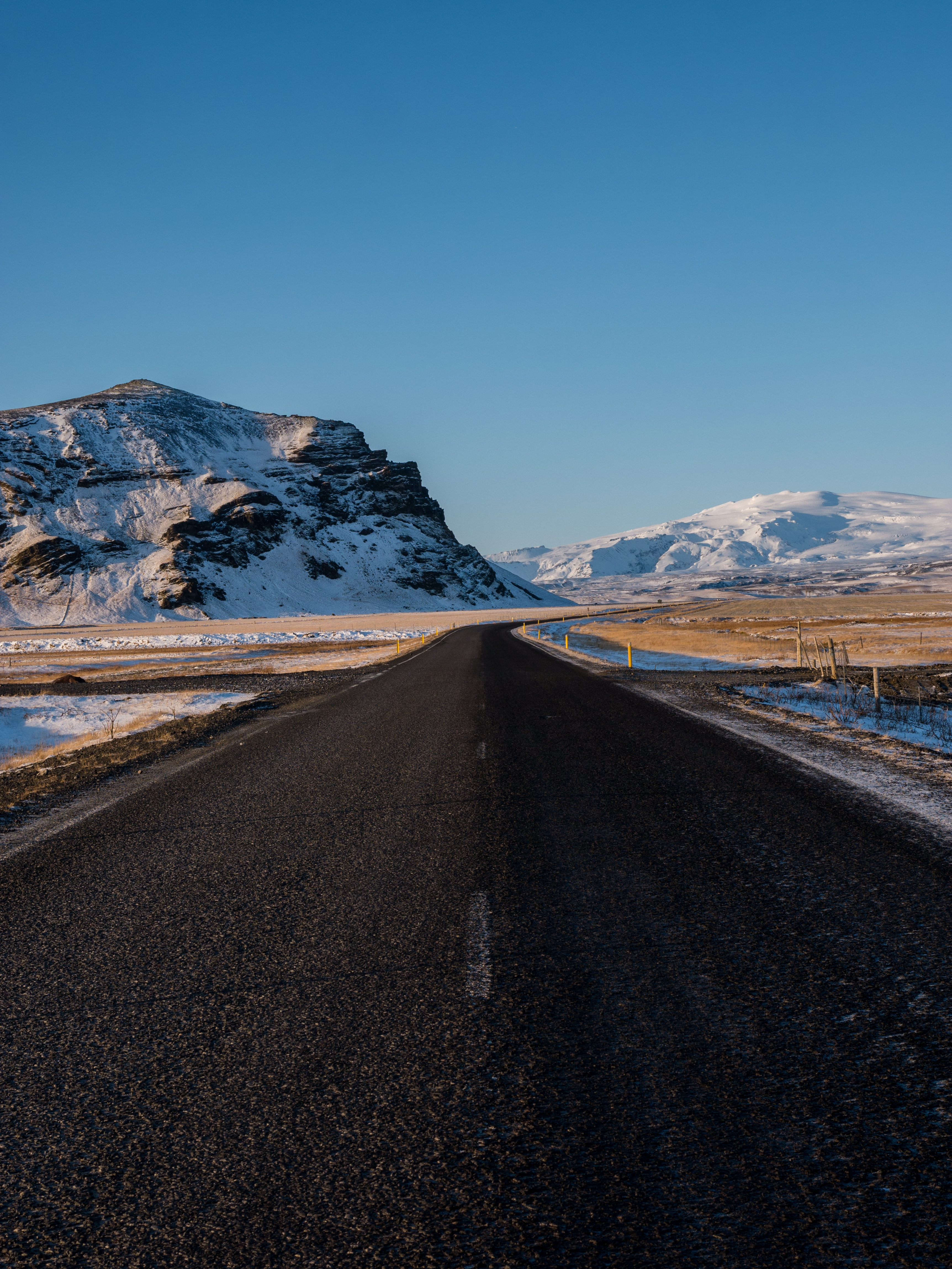 empty concrete road with snow capped mountain background