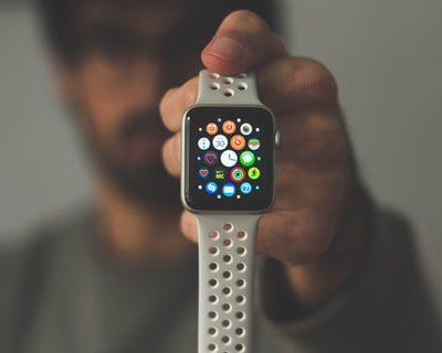 person holding silver aluminum case apple watch apple watch teams background