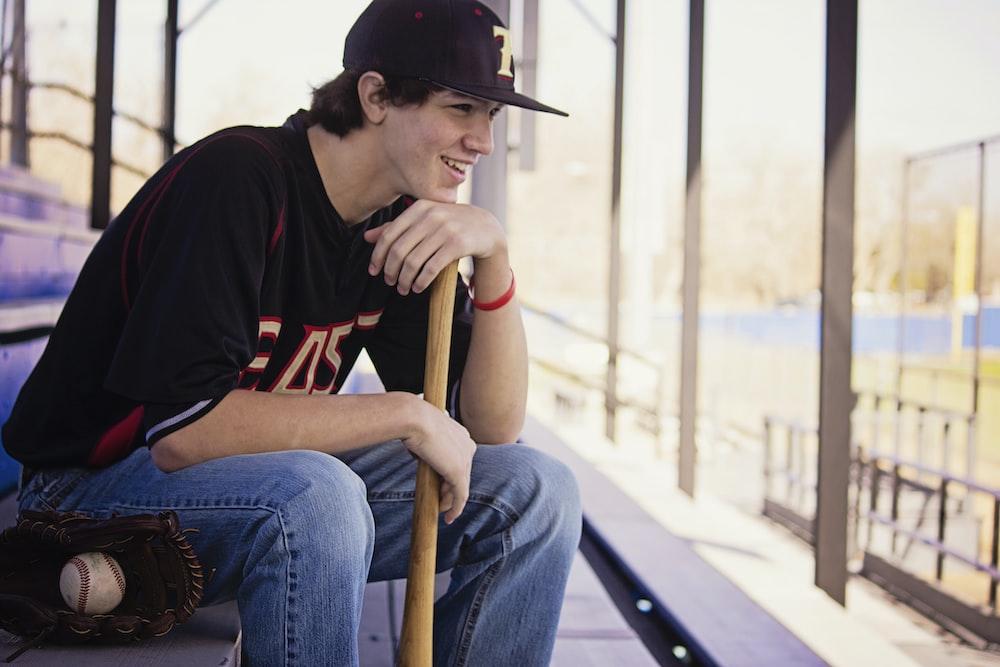 man sitting on bench holding baseball bat
