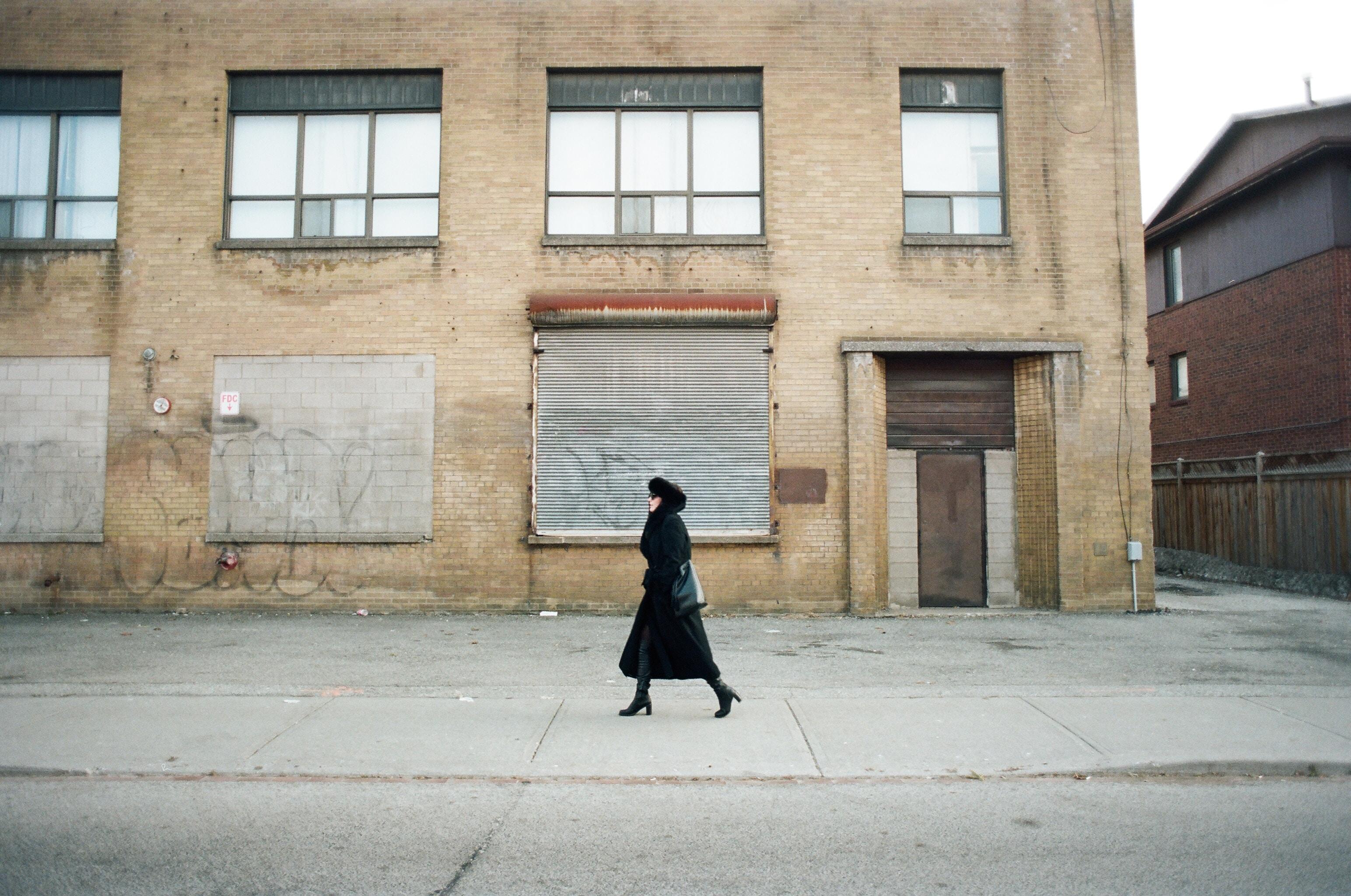 woman waking on gray pavement