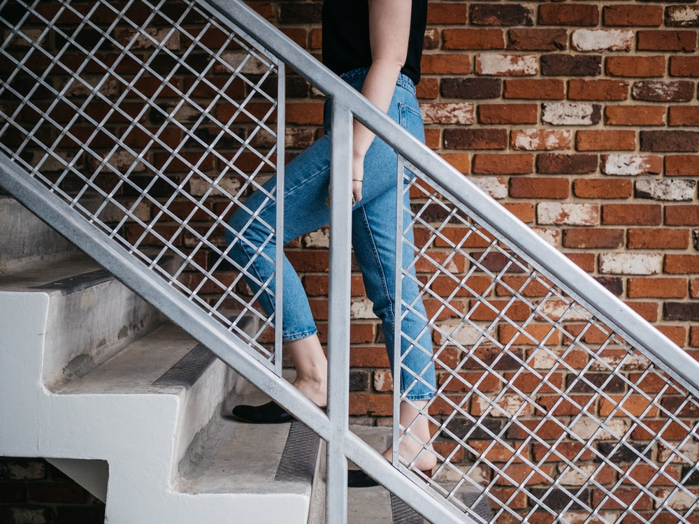 woman walking on stair near railling and wall