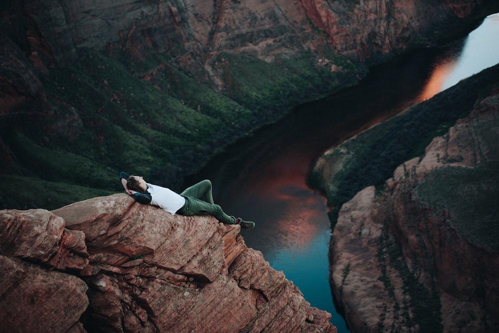 man lying on brown mountain near body of water