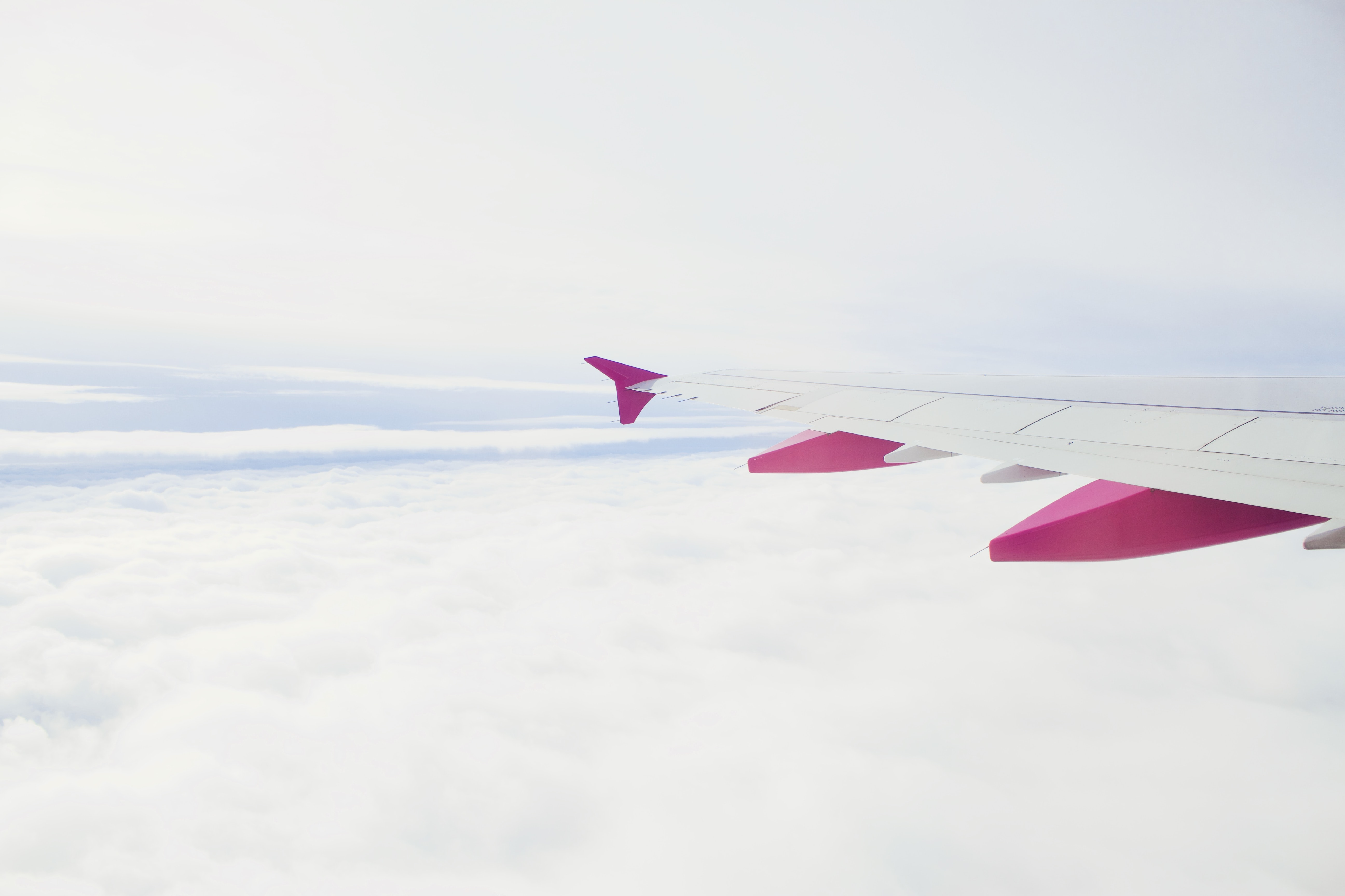 white and pink plane flying during daytime photography