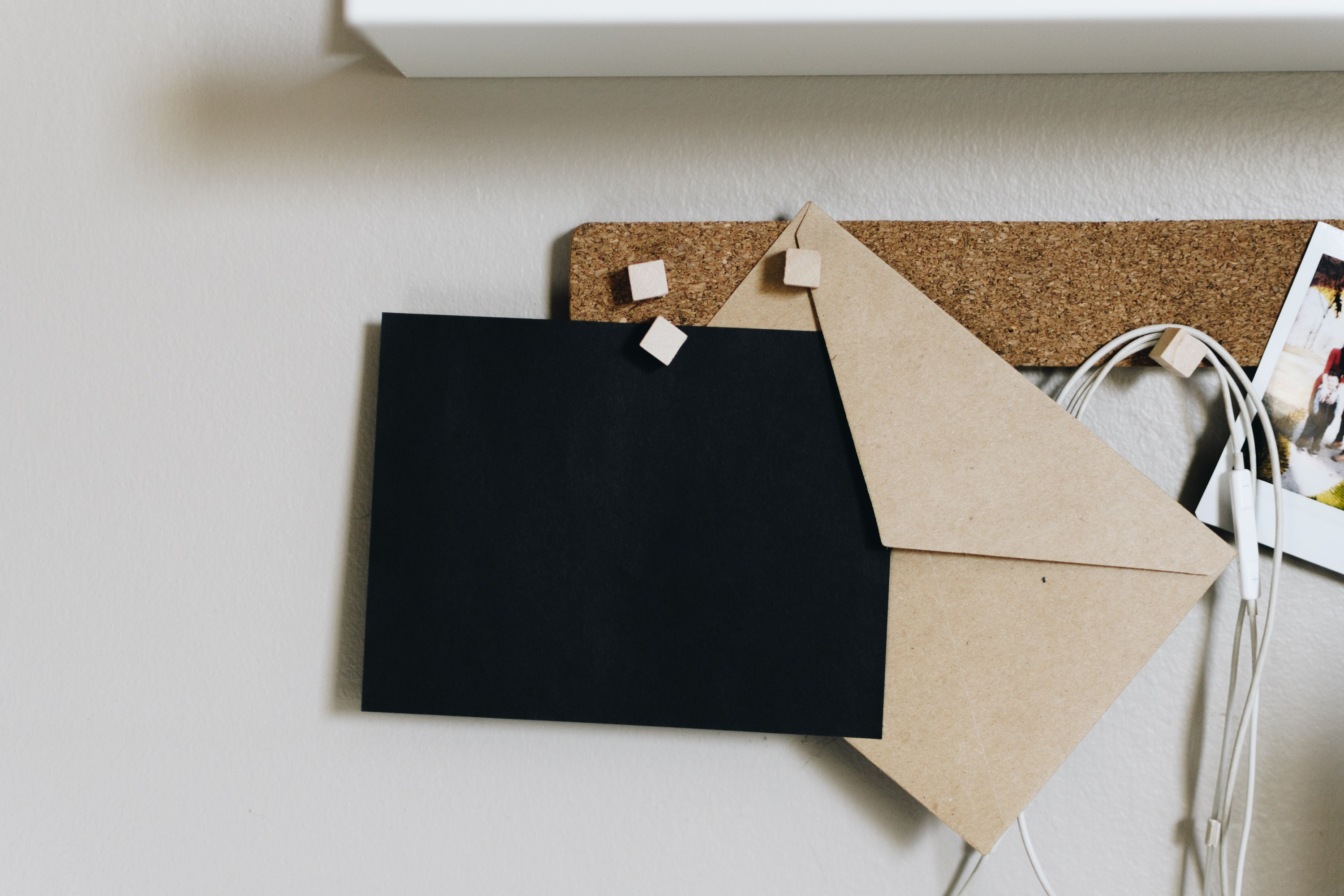 black and brown envelopes on cork board