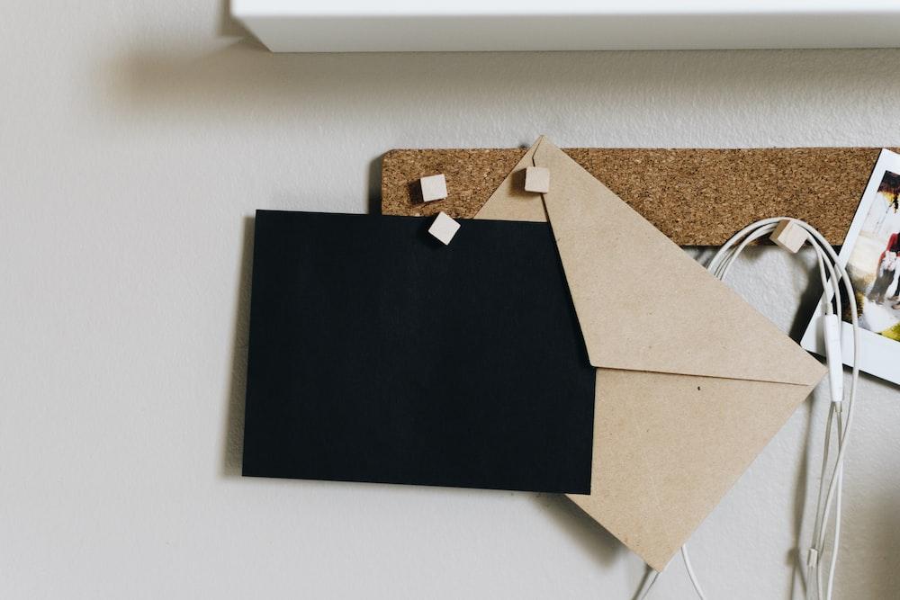 black and brown envelopes on cork board