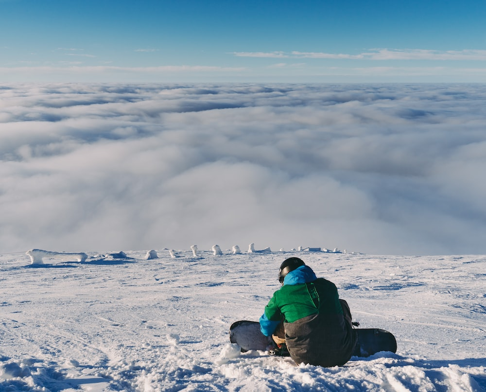 person holding snowboard while sitting on snow