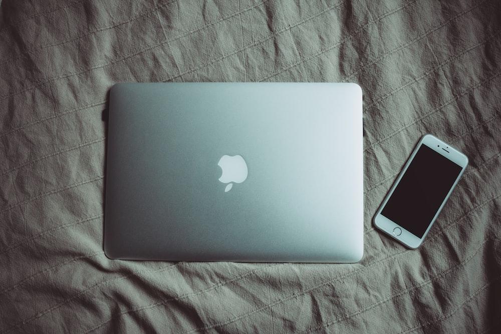 silver MacBook beside post-2014 iPhone