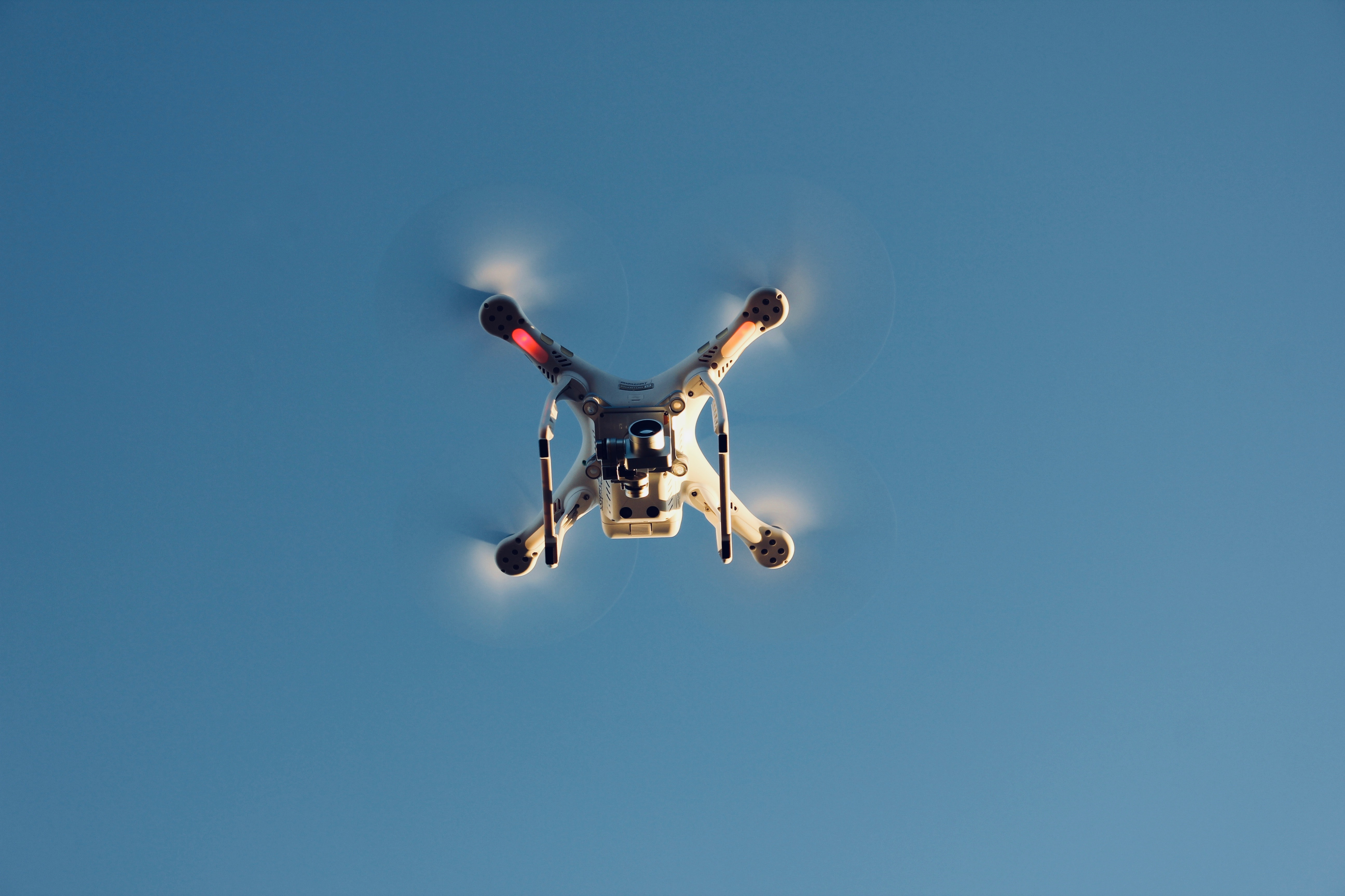 low angle photography of RC quadcopter at mid air