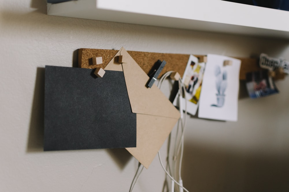 brown cork board with papers