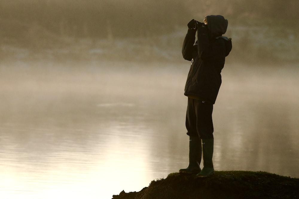 man on cliff looking at binoculars