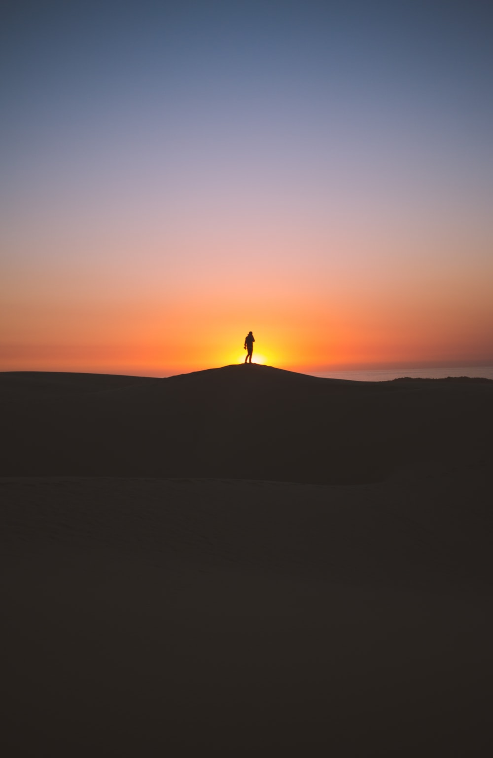 silhouette of person standing on hill