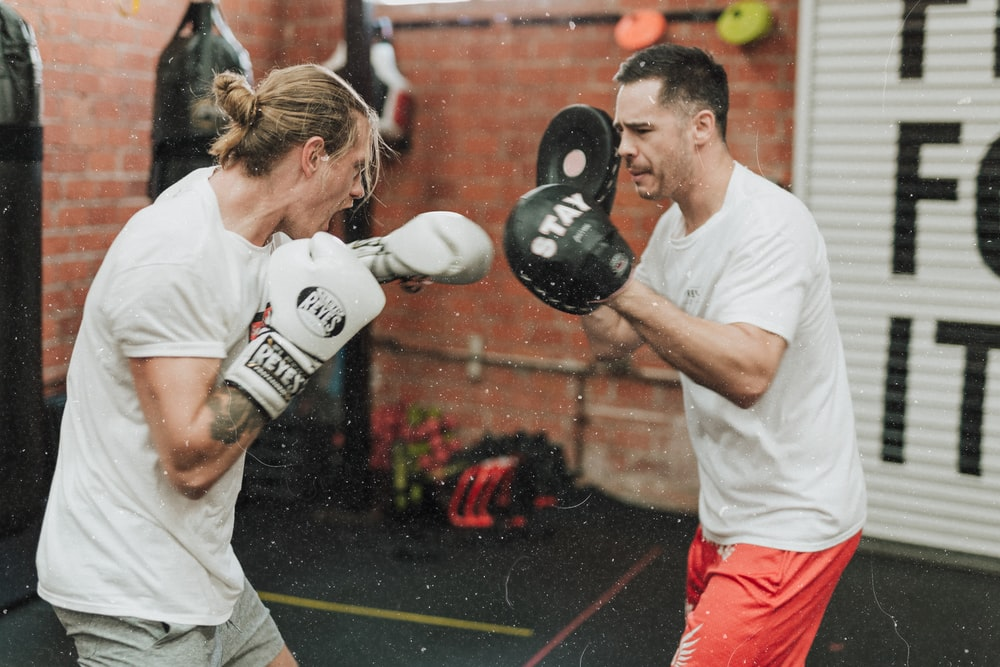 two men sparring inside boxing gym