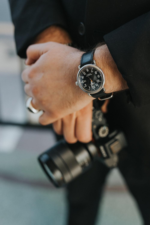 man wearing silver analog watch