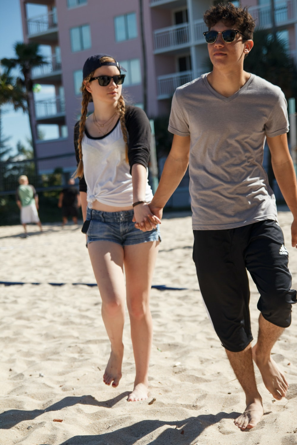 woman in white crew neck t-shirt and black shorts standing on white sand during daytime