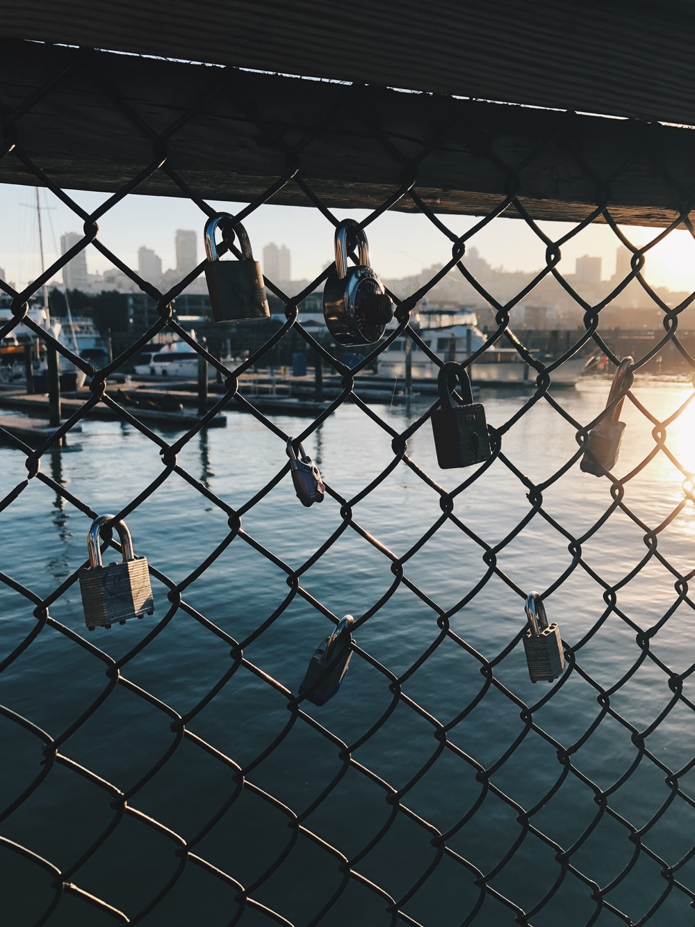 gray chain link with padlock over body of water