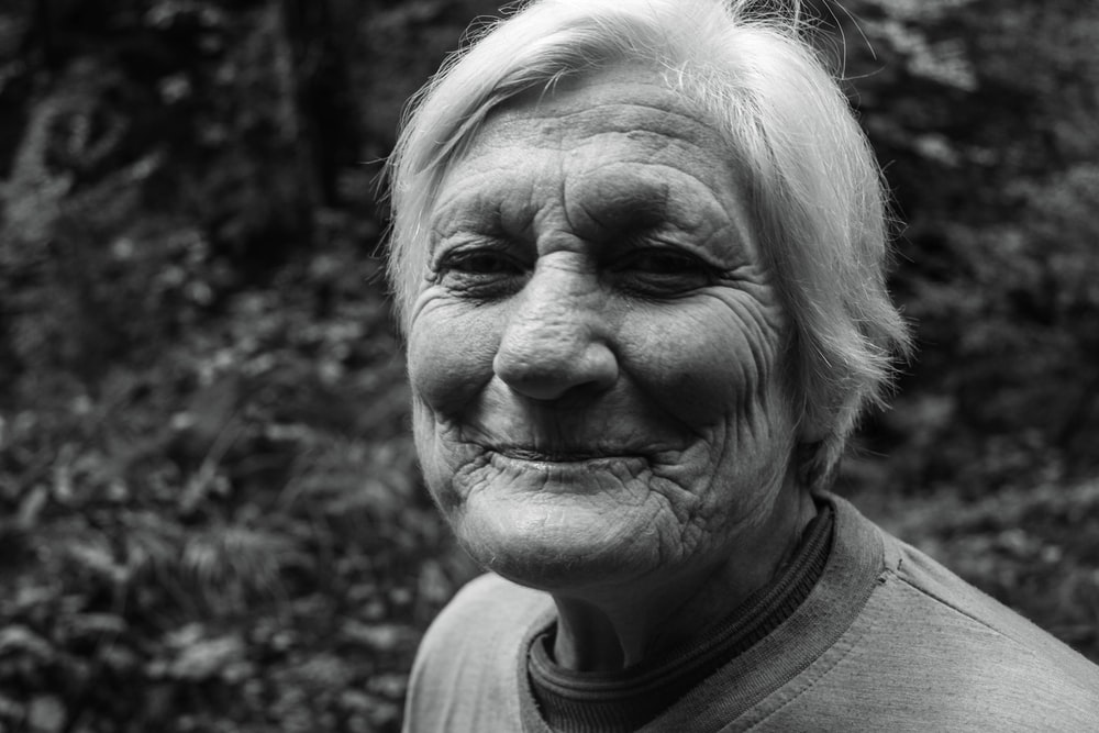 grayscale photo of smiling woman in crew-neck T-shirt