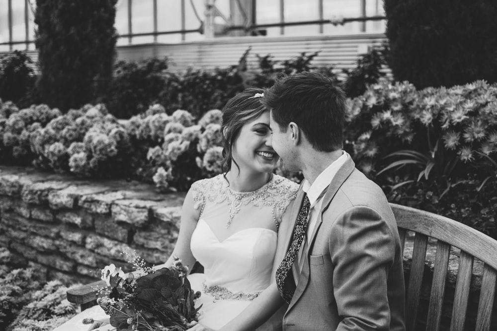 grayscape photo of newlywed sitting on bench