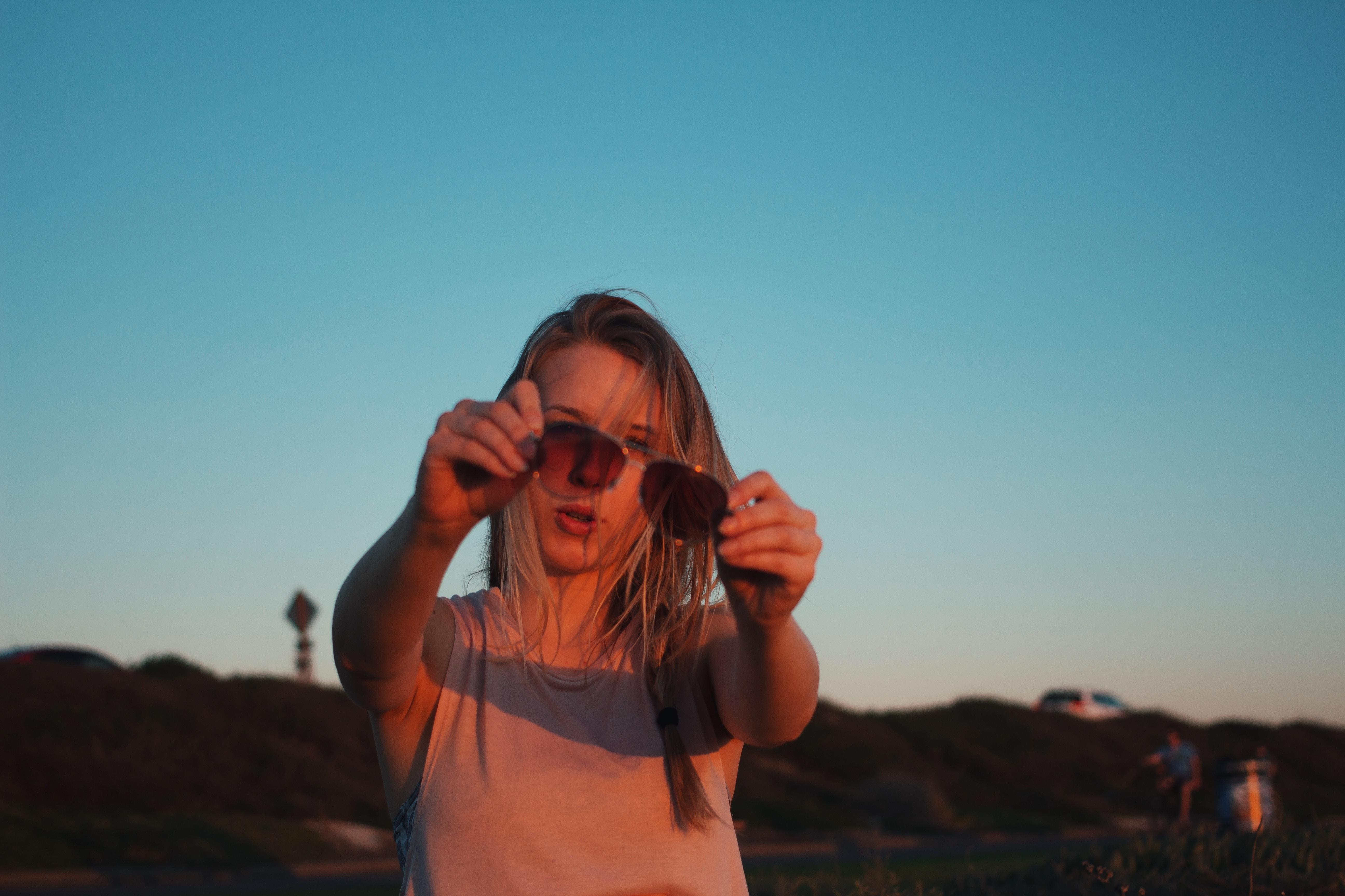 woman holding Aviator-style sunglasses