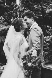 grayscale photo of couples kissing and wearing wedding dress