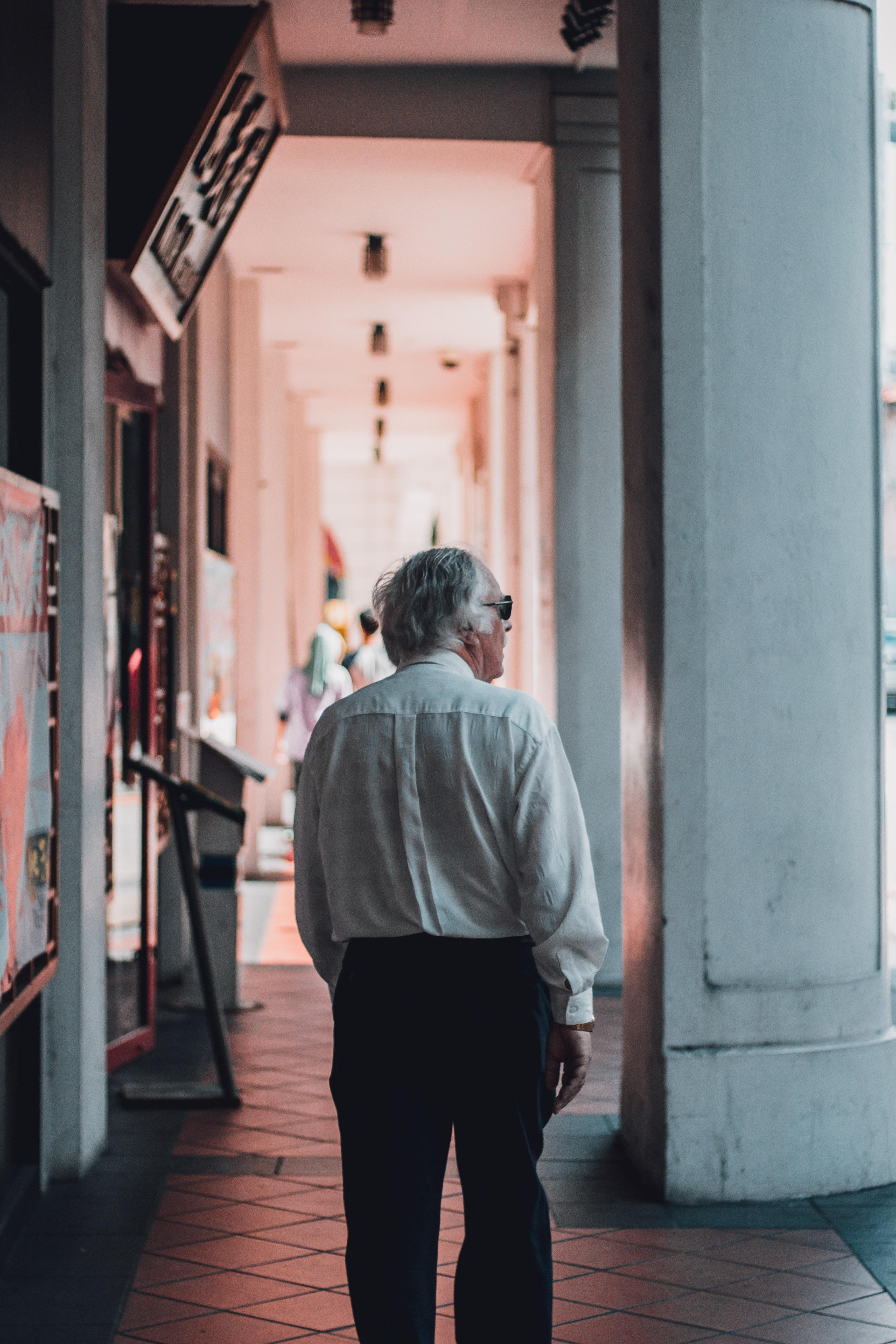 man wearing white dress shirt walking on hallway