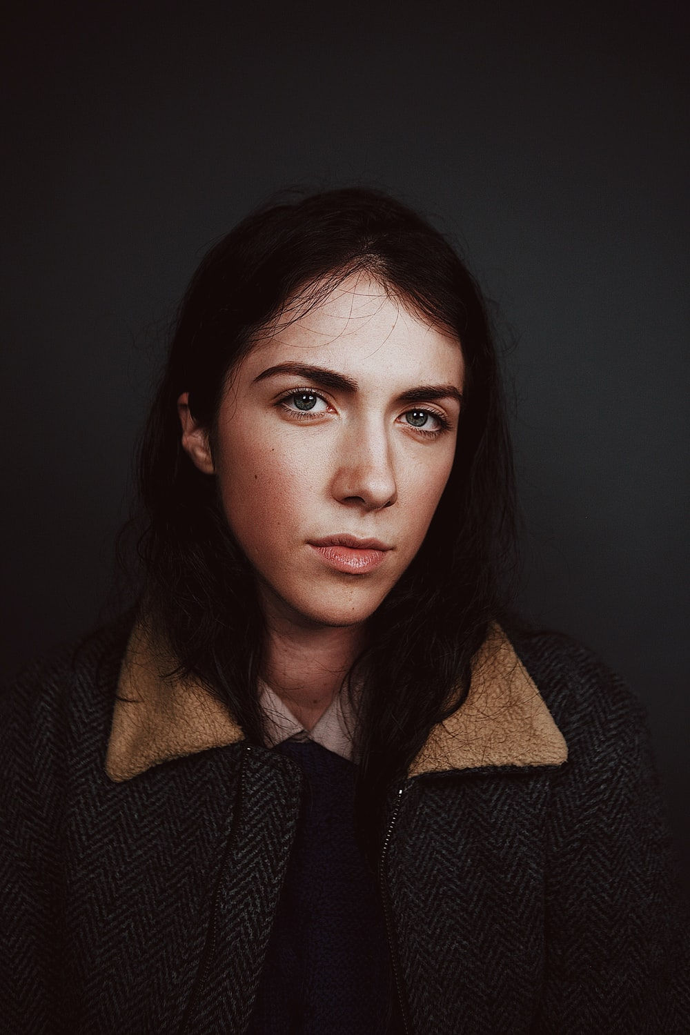 portrait photograph of woman in gray and brown coat