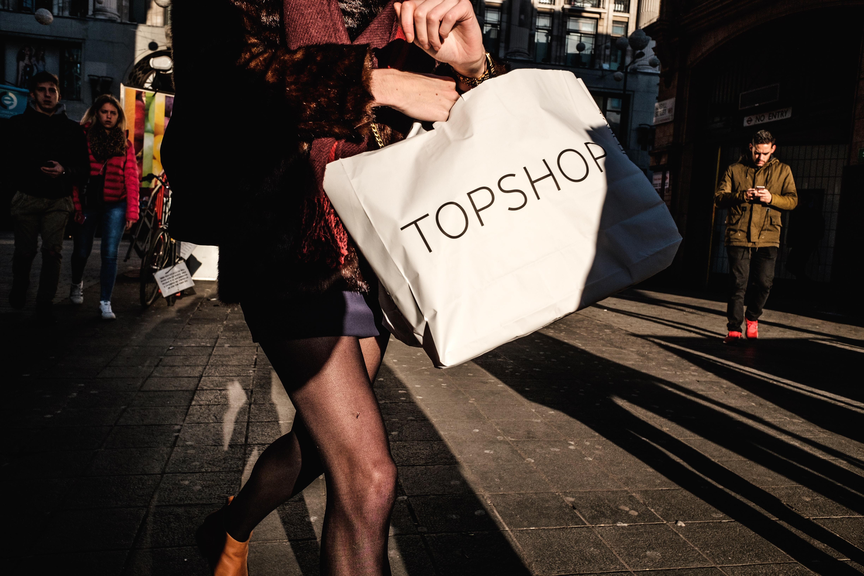 woman carrying white TopShop paper bag near man wearing brown jacket