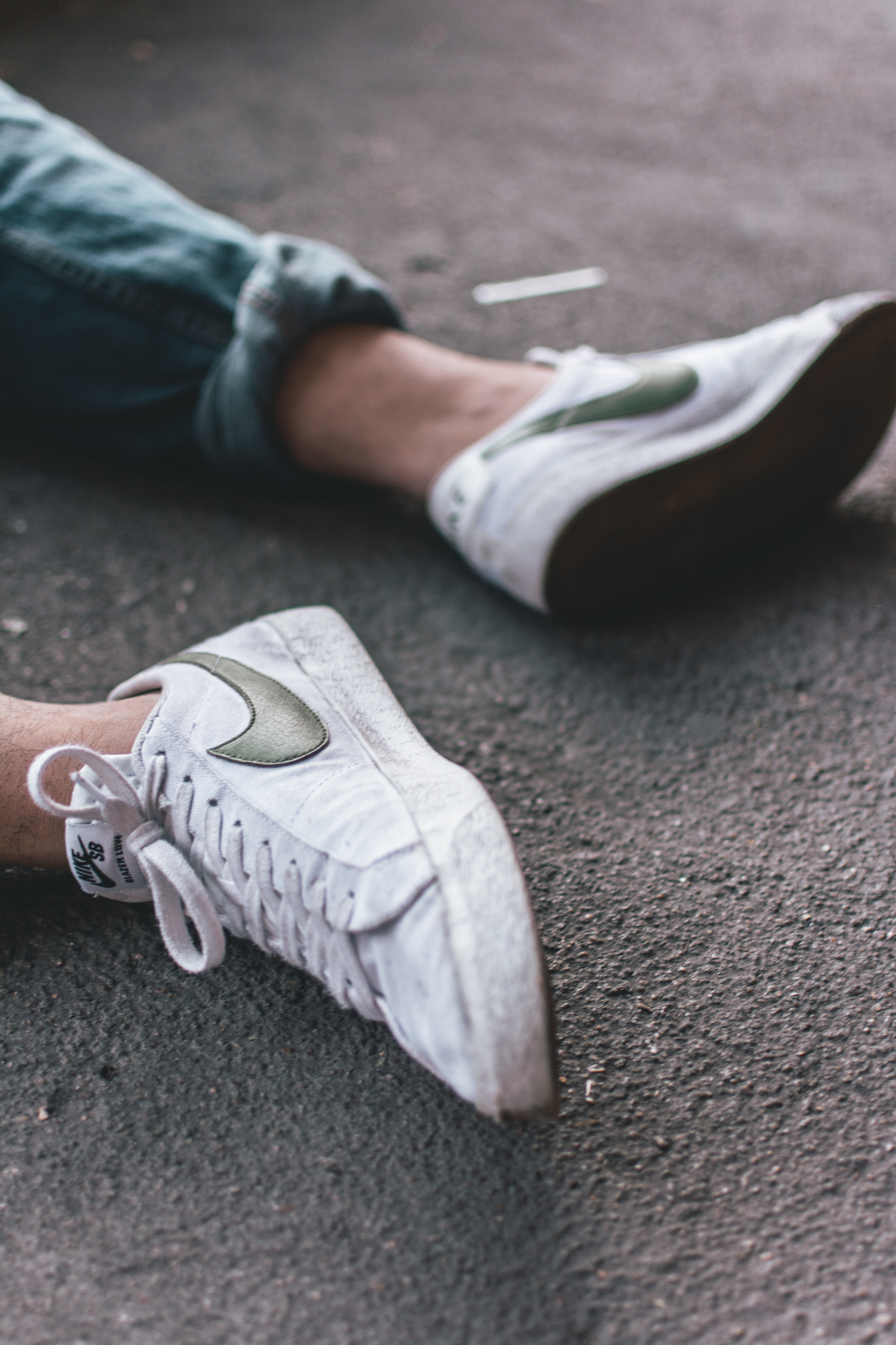 person wearing pair of white Nike sneakers