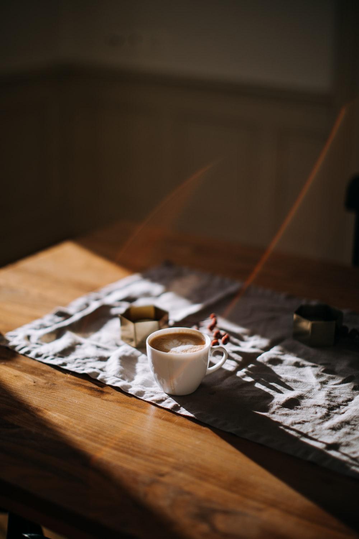 coffee mug on top of tablecloth beside ashtray