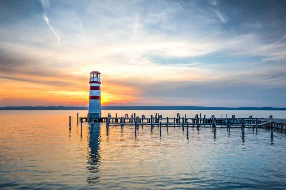 photo of white and red lighthouse beside wooden beach dock under clear blue sky