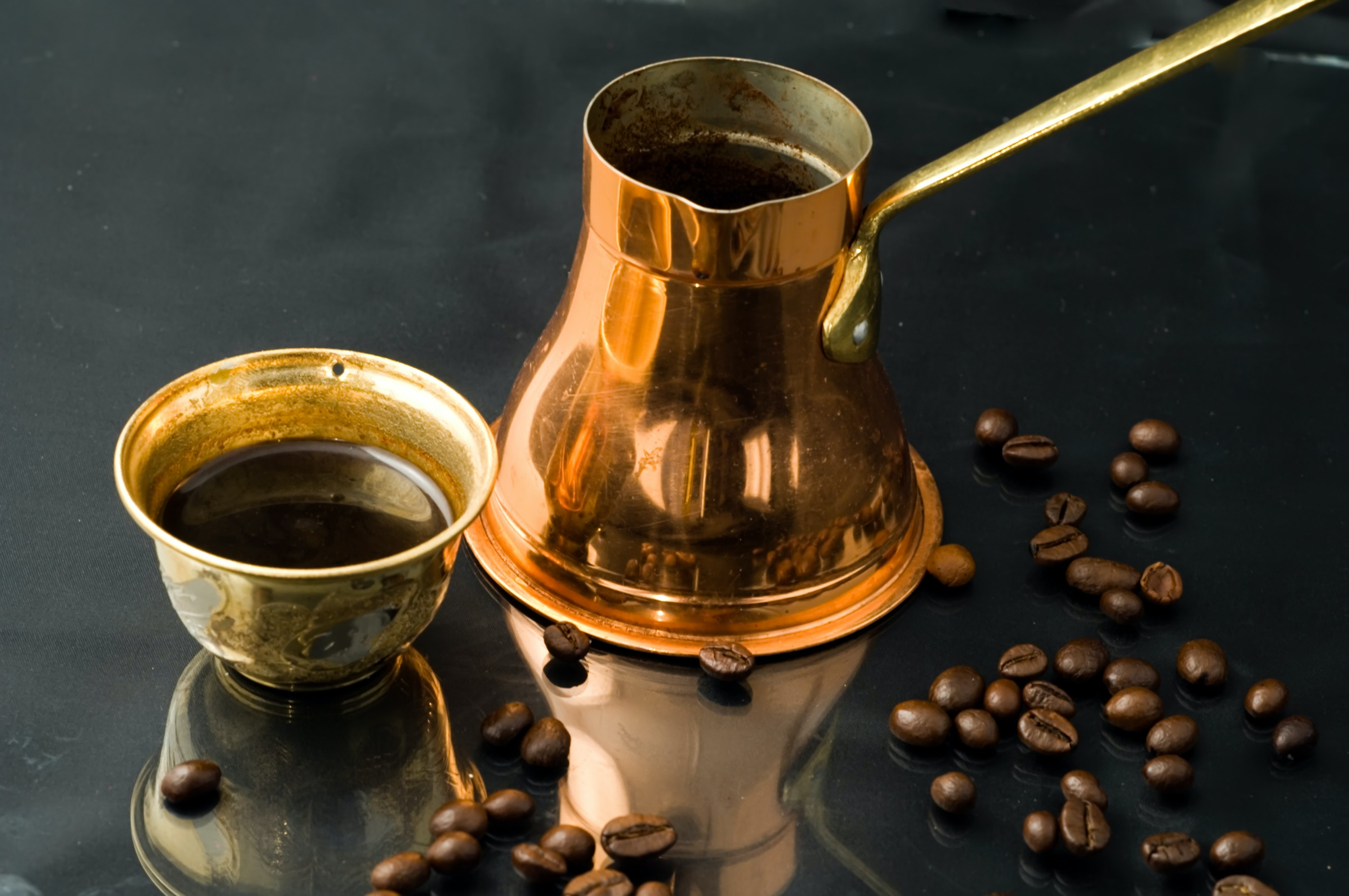 cezve bot and lid on glass surface with roasted coffee beans