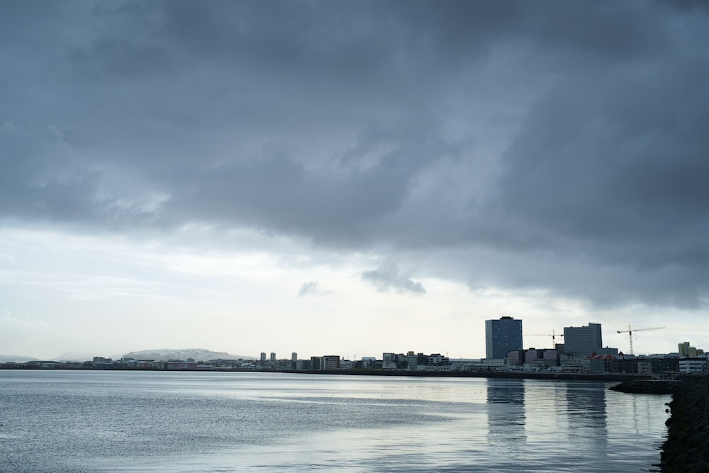 body of water near city buildings under cloudy sky during daytime