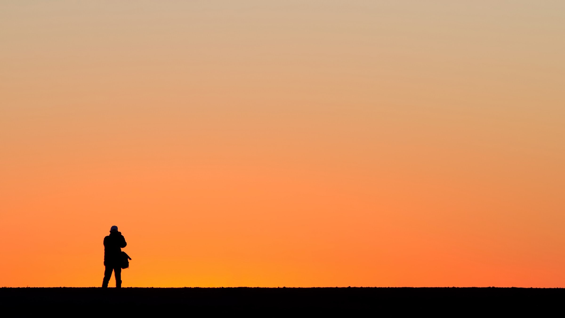 silhouette of standing person under orange sky