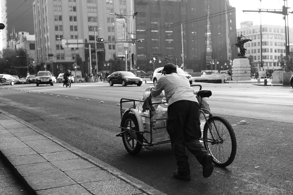 man in white dress shirt and black pants riding on bicycle in grayscale photography