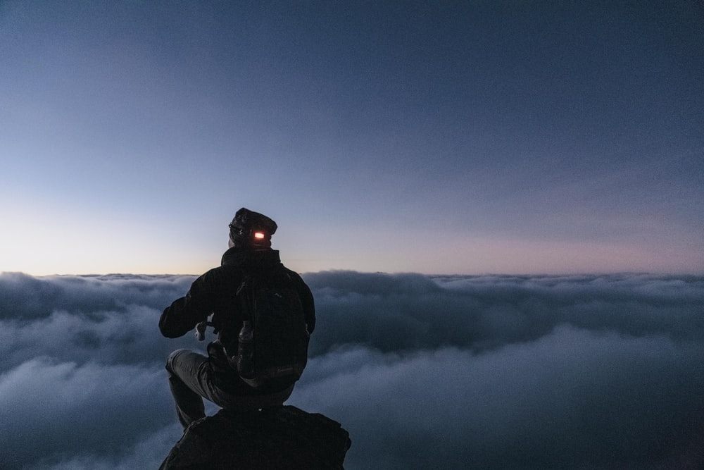man sitting on top of the mountain