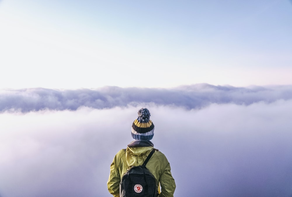 person looking thru sea of clouds