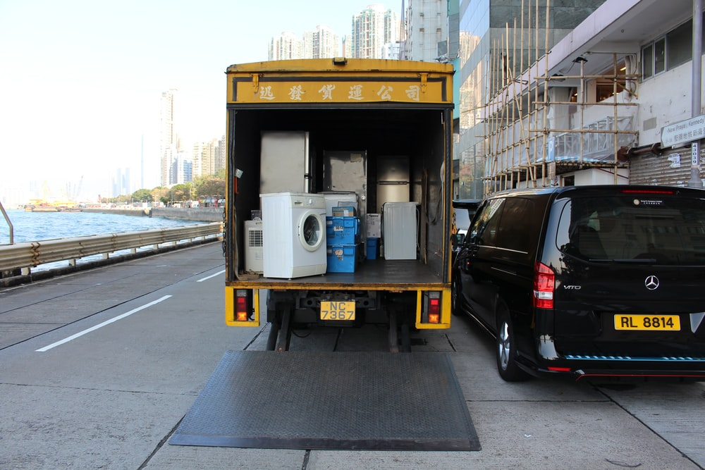 white front-load washer in yellow delivery truck
