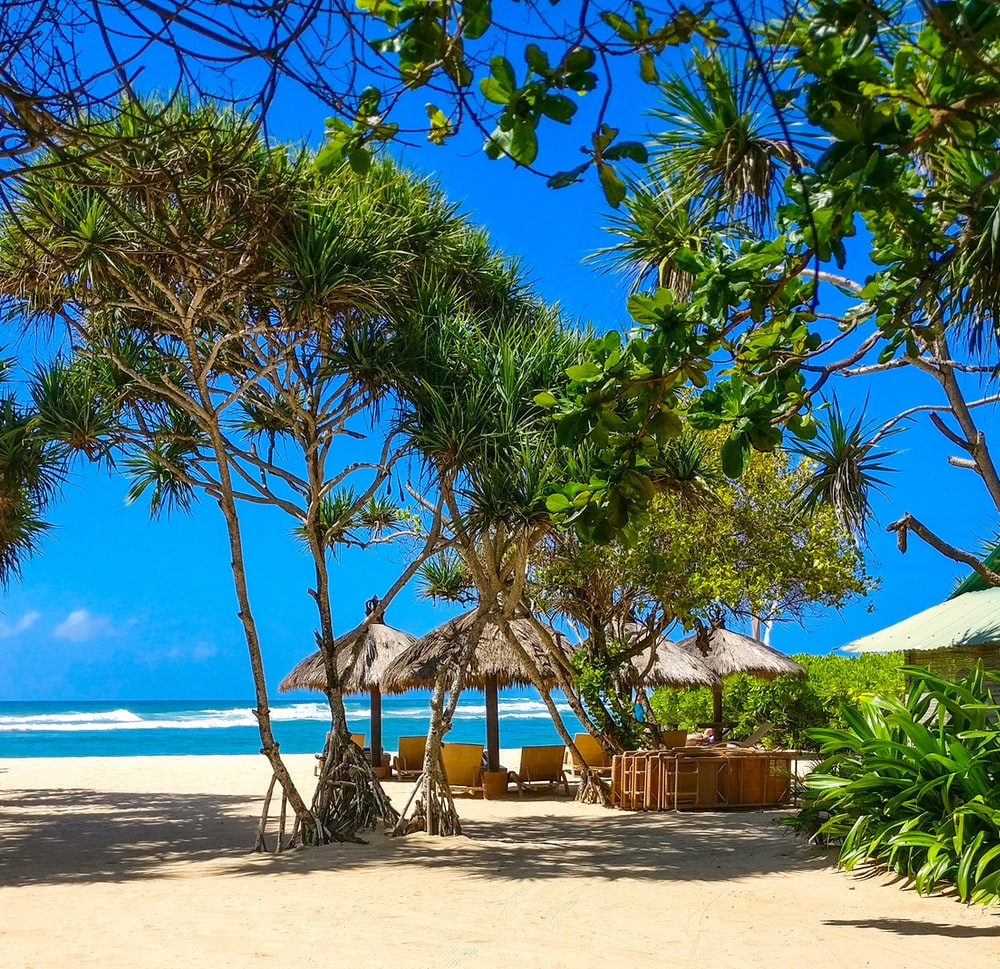 four huts at beach under blue skies during daytime