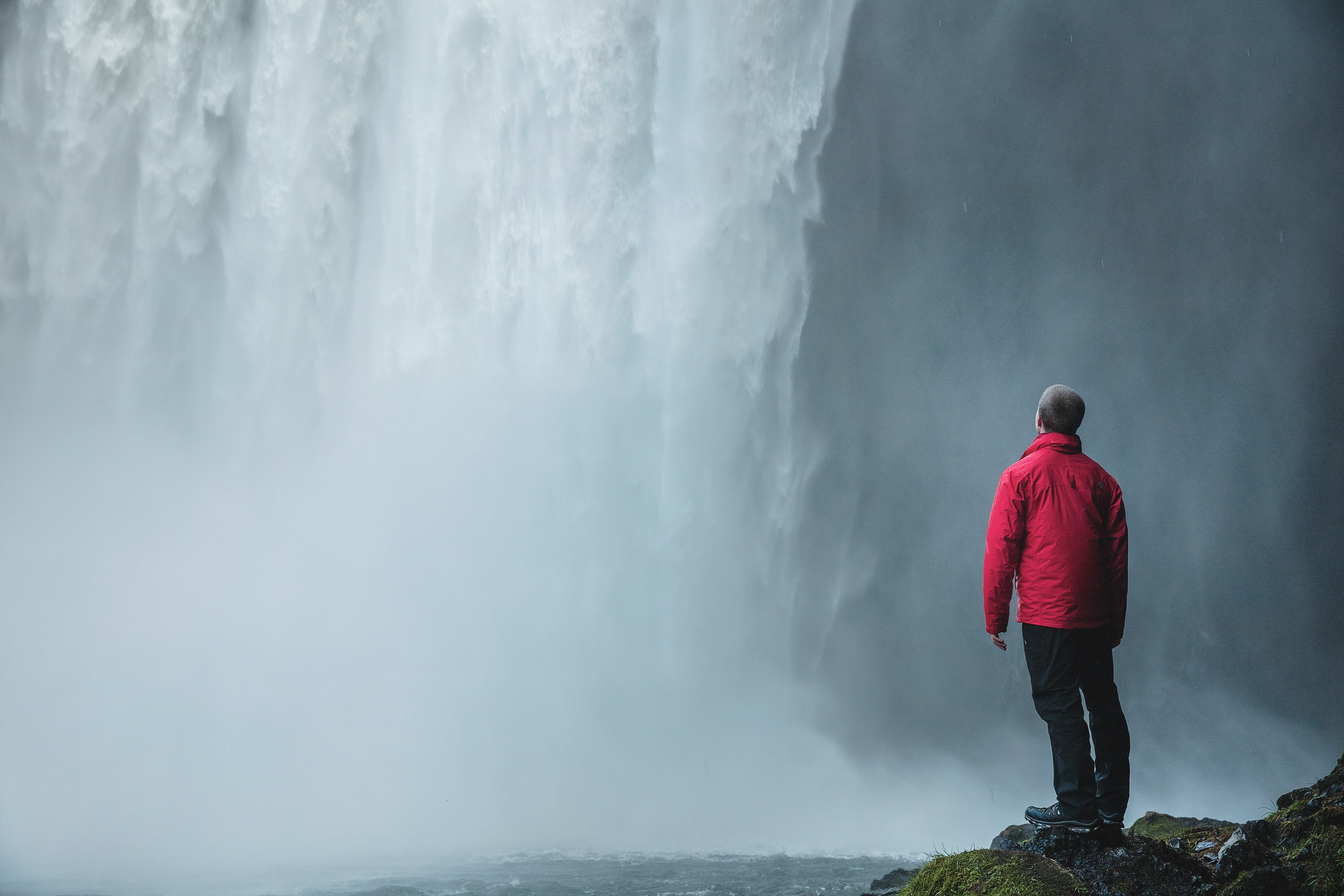 man standing on a rock facing waterfalls