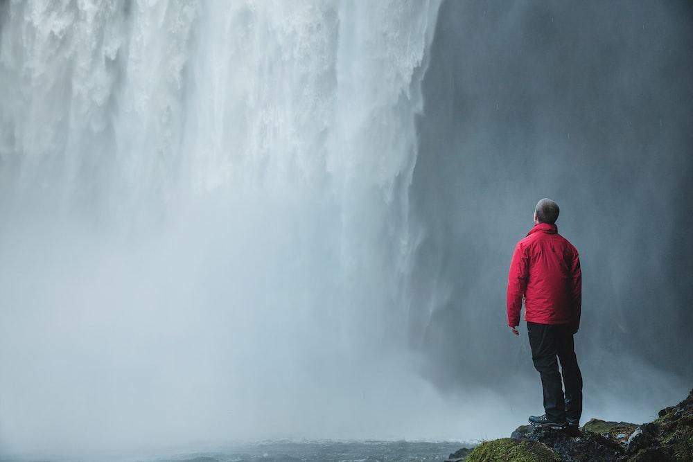 man standing on a rock facing waterfalls