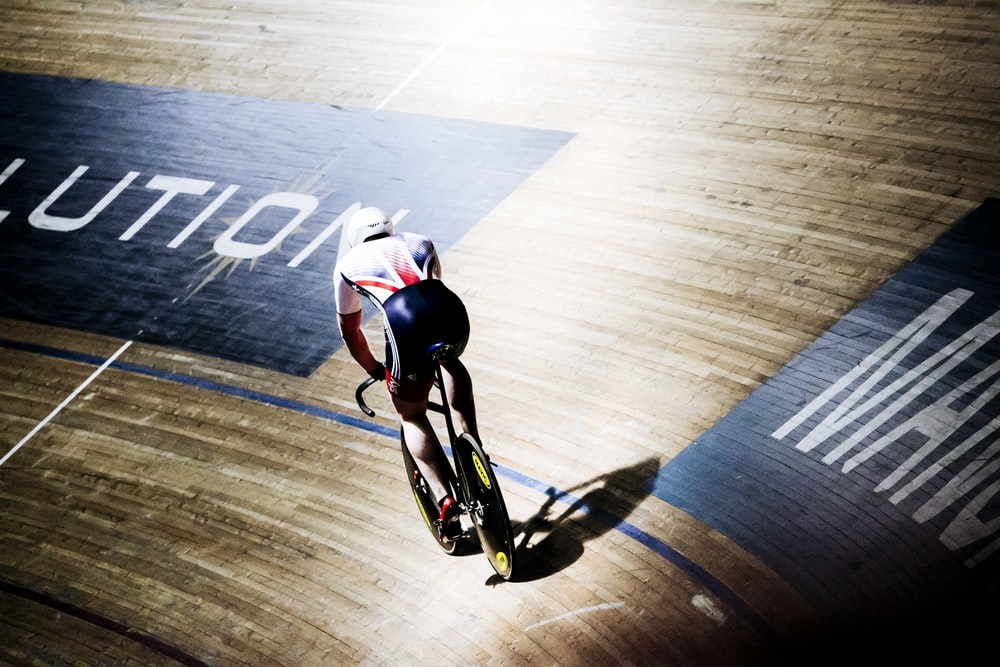man riding bike on indoor cycling field