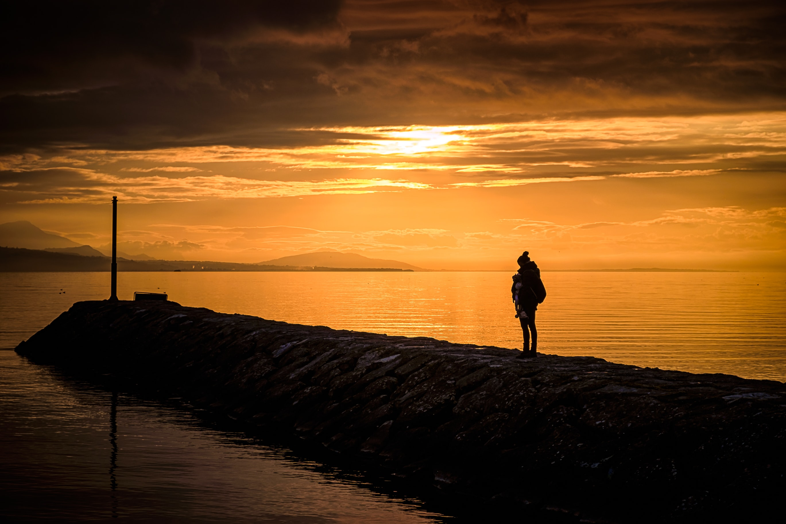 silhouette of person standing near body of water
