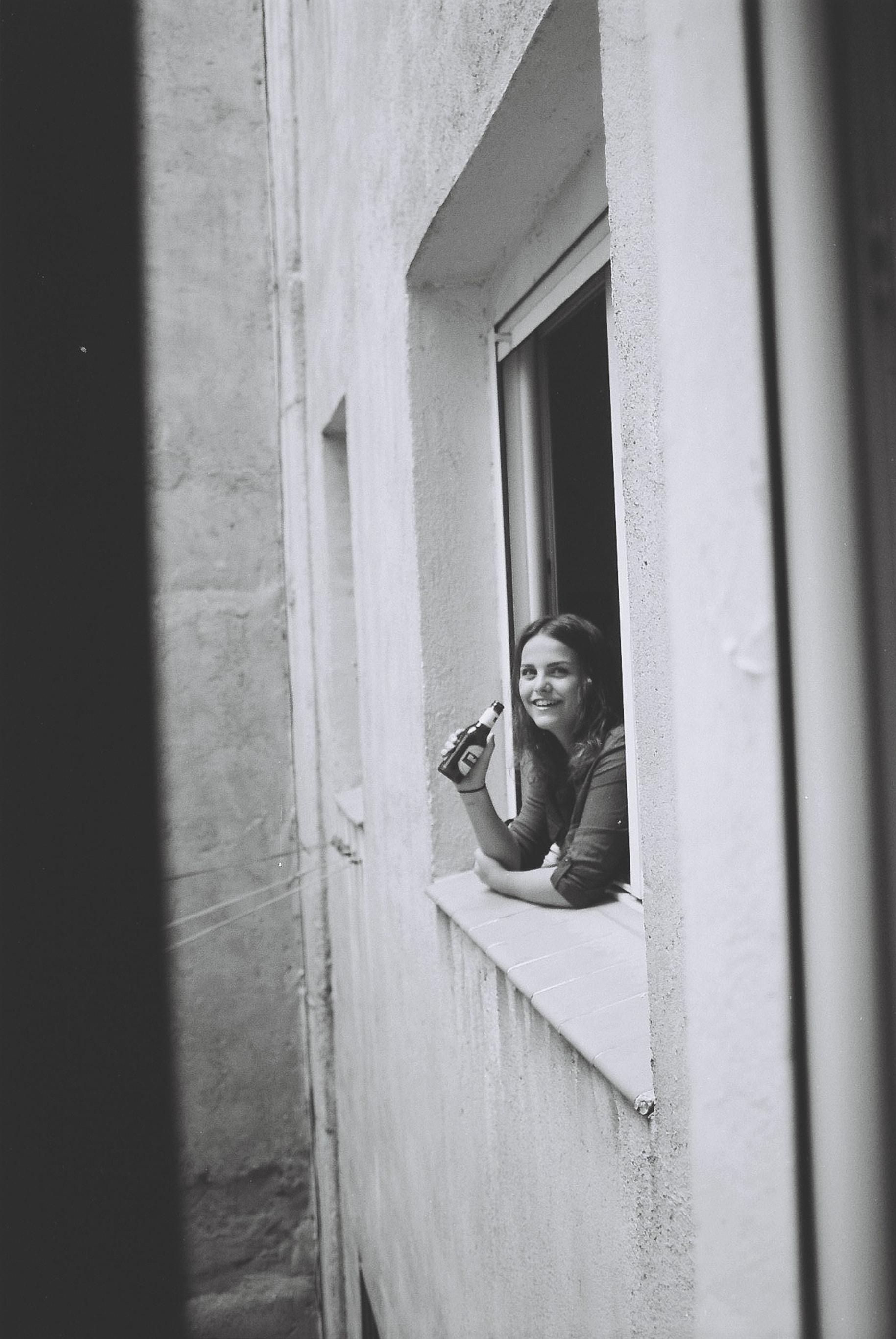 woman holding beer bottle on window
