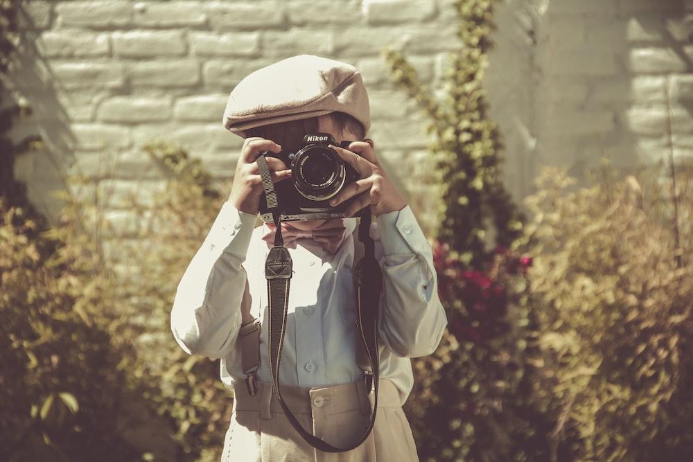 boy holding black DSLR camera