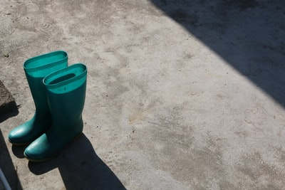 pair of green rain boots on gray pavement
