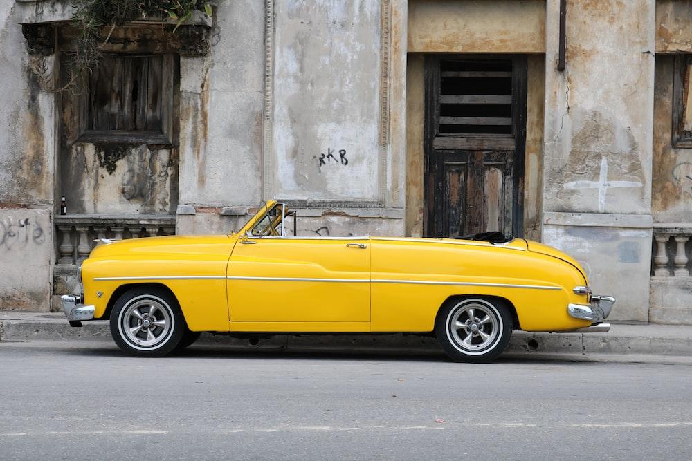 parked vintage classic car near concrete wall