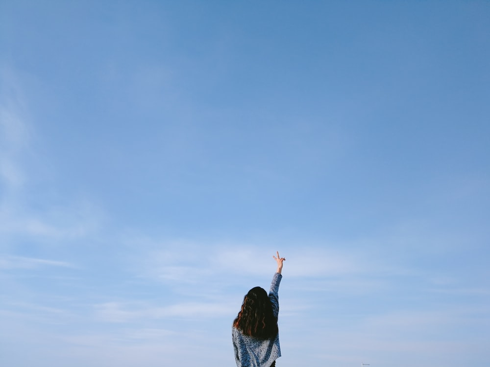woman in gray top performing peace sign under blue sky