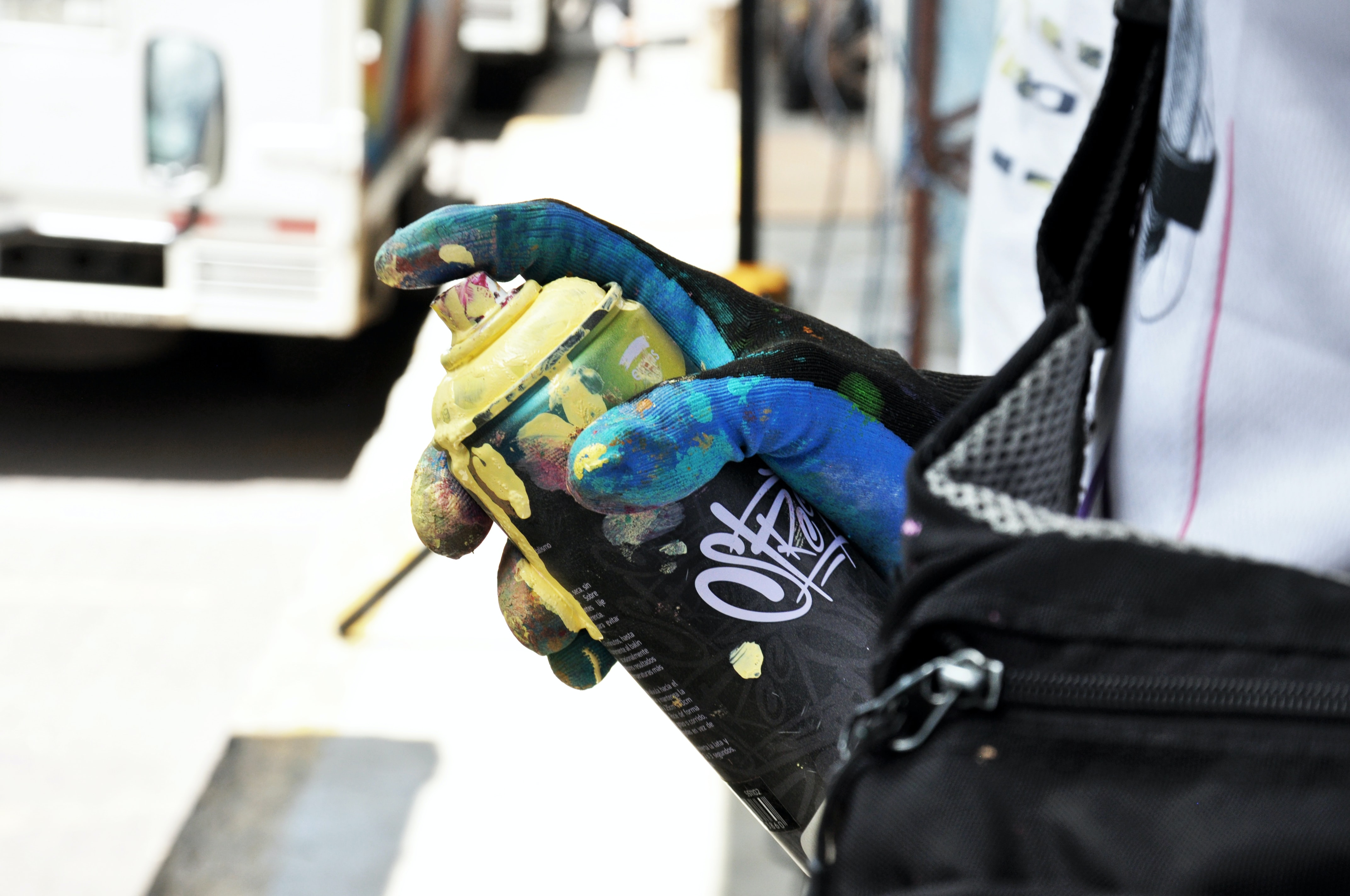 person holding black and yellow spray bottle