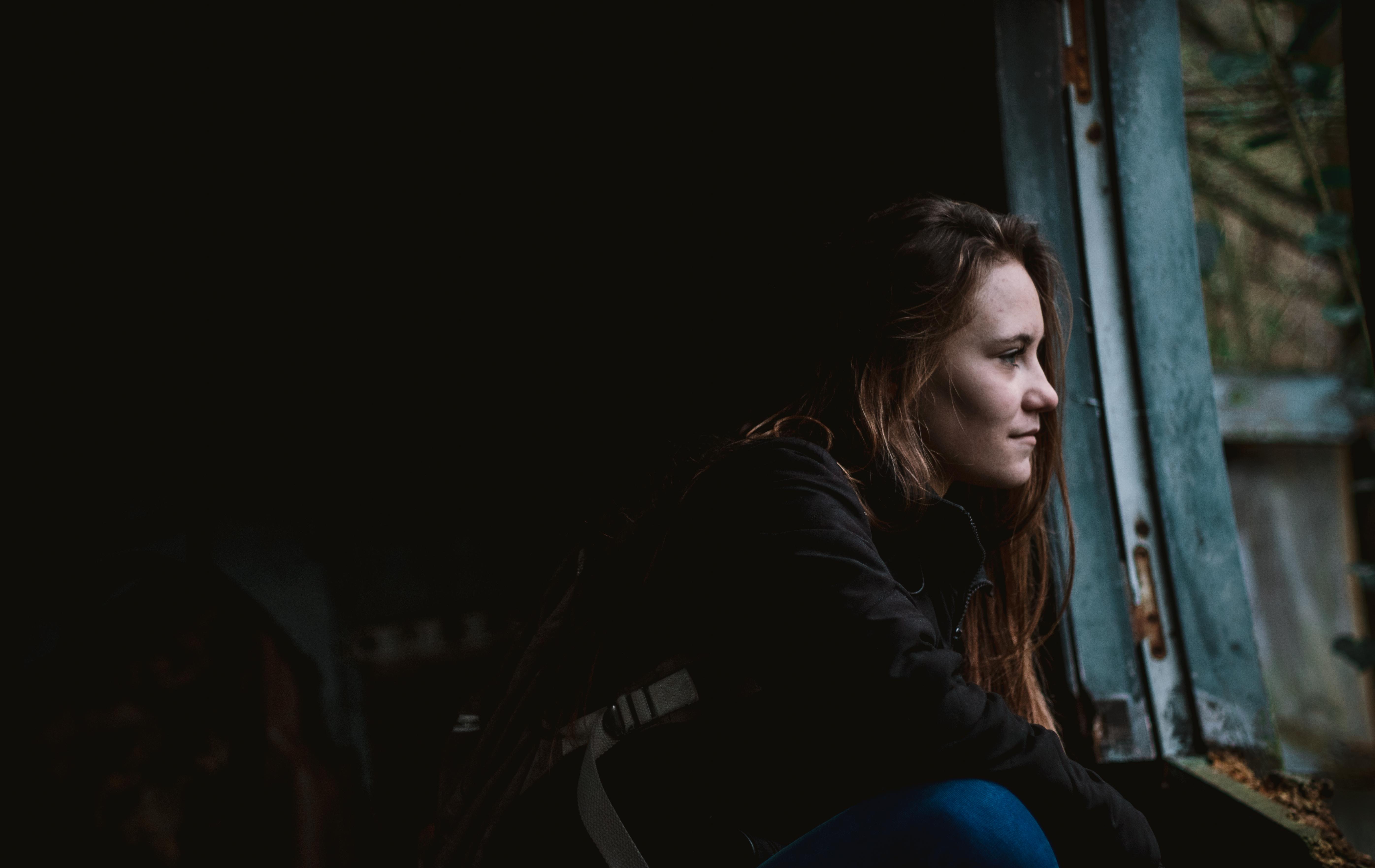 woman sitting next to window